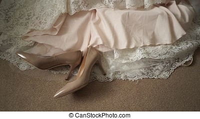 Shoes lie on the background of the bride's dress-2