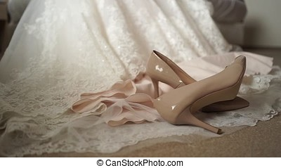 Shoes lie on the background of the bride's dress-3