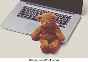 beautiful cute teddy bear and cool laptop on the wonderful...