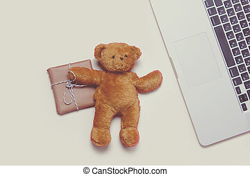 beautiful small gift, cute teddy bear and cool laptop on the...