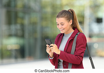 Young businesswoman using phone on the street - Single happy...