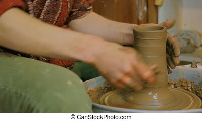 Professional potter shaping part of kettle with special tool...