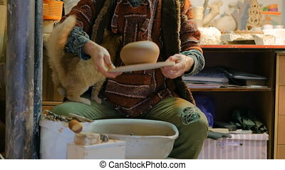 Professional male potter working in workshop, studio -...