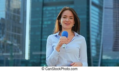 Young girl TV reporter is broadcasting on modern city...