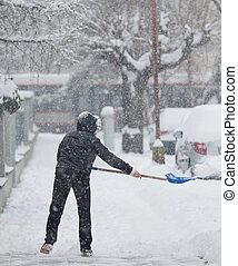 Woman shoveling snow from a sidewalk after a heavy snowfall...