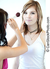 pretty young woman having powder applied by a make-up artist/beautician