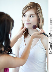 pretty young woman having powder applied by a make-up