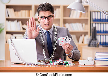 Young businessman addicted to online gambling cards playing...