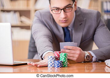 Businessman gambling playing cards at work