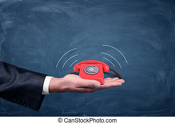 A businessman's palm hold a small red retro dial phone with lines showing soundwave emissions.