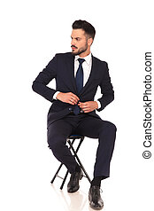 young business man sitting on chair and buttoning his suit -...