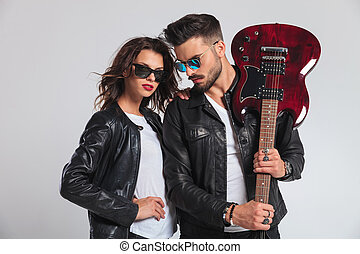 man showing his electric guitar with woman by his side