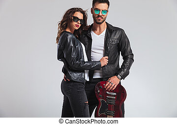 fashion rock and roll couple standing with electric guitar