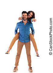 casual man carrying his woman while she is pointing - happy...