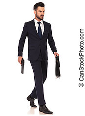 walking young elegant assasin holding gun and briefcase -...
