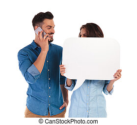 happy casual man talking on the phone and looks at woman...