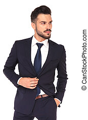side view of a young business man buttoning his suit - side...