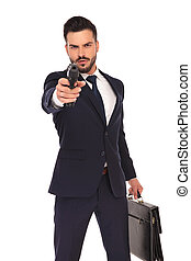 serious young hitman pointing and aiming his gun to the...