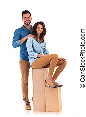 smiling casual man standing behind seated woman on wooden...