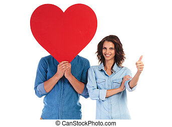 woman makes ok sign near man covering face with heart