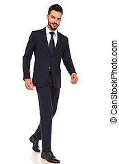side view of a modern smiling business man walking