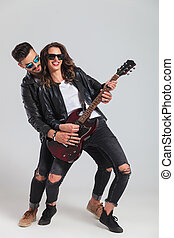 laughing woman plays electric guitar with her man