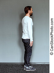 Full length profile view of an actor on grey backdrop in...
