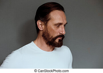 Man actor on grey background with severe face. Beardy mature...