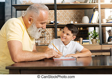 Caring grandfather giving tips on grandsons home assignment...