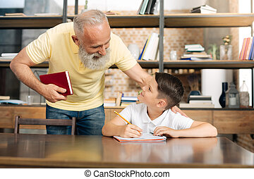 Caring grandfather checking his grandsons progress in...