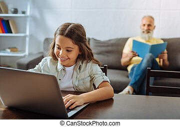 Little girl using laptop while her grandfather reading a book