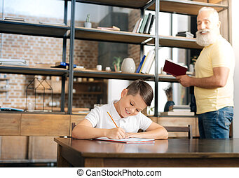 Grandfather carrying out dictation for his grandson -...