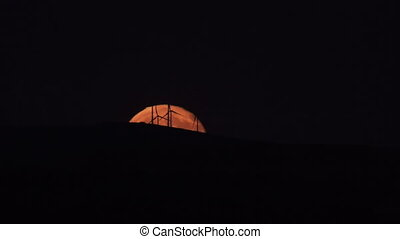 Full moon rising over modern windmills - Long shot of full...