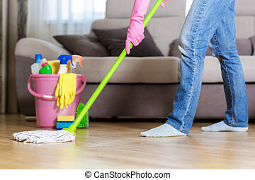 woman in protective gloves using a wet-mop while cleaning...
