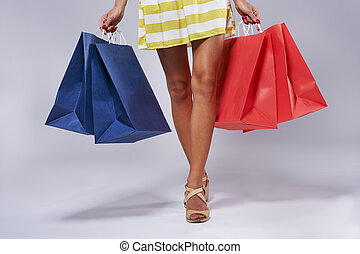 Blue and red shopping bags held by a woman