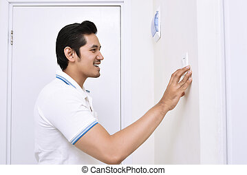 Handsome asian man turning off the light with wall switch in...