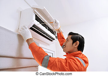 Young asian male technician repairing air conditioner with...