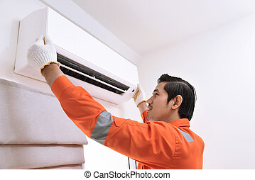 Young asian male technician repairing air conditioner at...