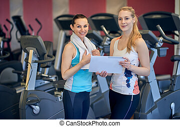 Two female athletes holding their traing plan - Attractive...