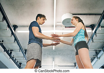 Beautiful young fit couple in modern gym. - Beautiful young...