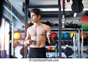 Hispanic man in gym resting, holding earphones, listening...