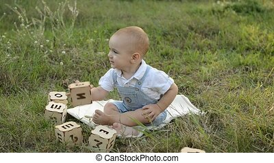 little child playing with dices in the park - little child...