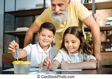 Grandfather watching grandchildren washing brush and...