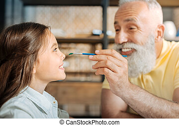 Cheerful grandfather painting nose of his granddaughter -...