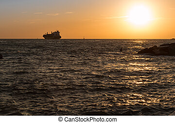 Silhouette of Cargo Boat in Choppy Sea at Sunset