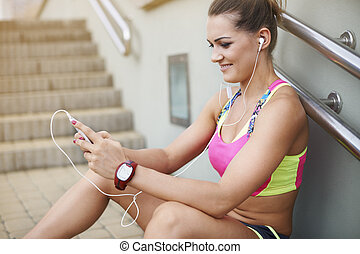 Woman in sports clothing resting on the steps
