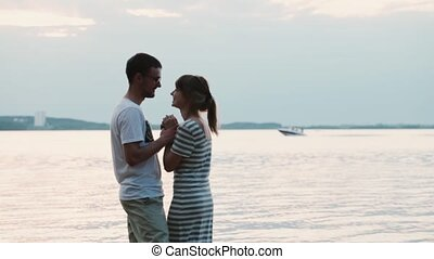 Beautiful young couple standing on the beach and kissing. Attractive man and woman hugging on the shore of the river.