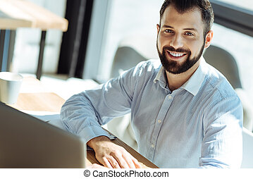 Charming young man smiling at camera while working in office