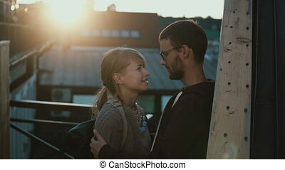 Young attractive couple standing on the balcony and talking...