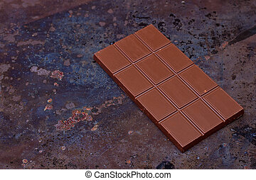 Milk chocolate bar on a black grunge background